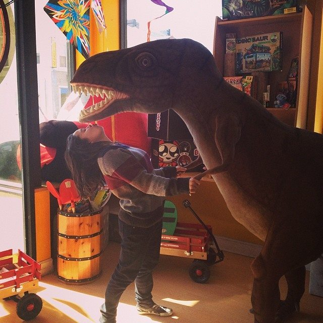 This blogger leaning in for a kiss with a big stuffed dinosaur (presumably a tyrannosaurus rex)