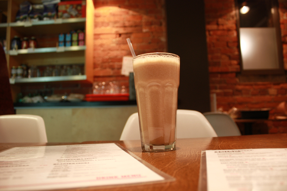 creamy and frothy glass of Butterscotch Ripple smoothie in front of one of the brick walls at Live Food Bar