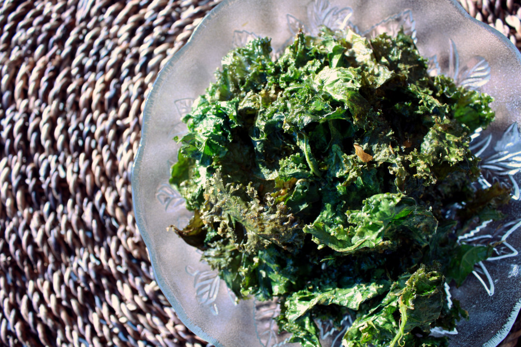 Overhead view of oven fresh kale chips, in a decorative class bowl