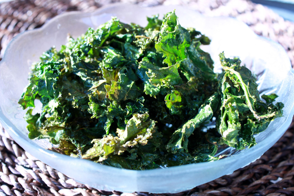 Bowl of crispy kale chips in a decorative glass bowl, sitting in the sunshine