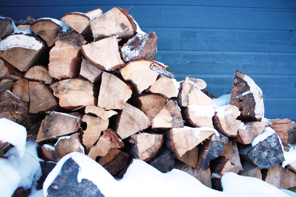 snow-dusted woodpile against a cottage in Muskoka