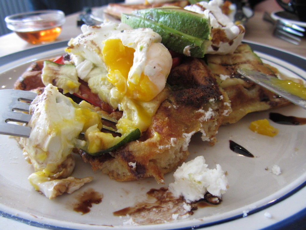 Side view of pesto waffles topped with poached eggs, roasted red pepper and zucchini, sliced avocado and drizzled with balsamic reduction (with bites taken out of them)