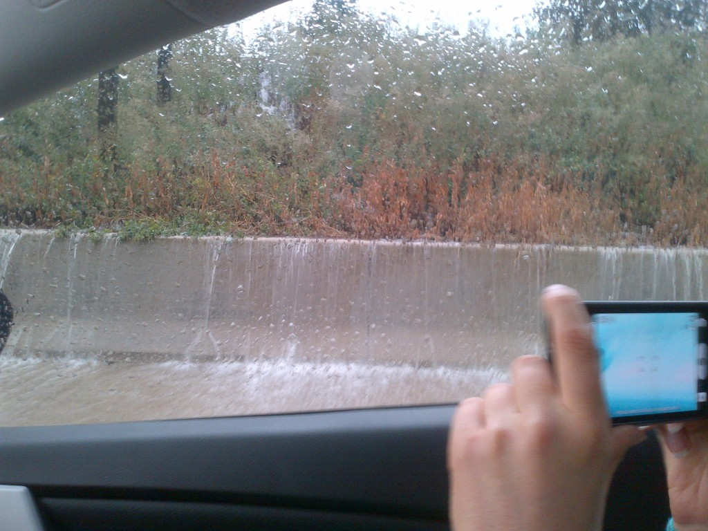 Water starts pouring over concrete barrier on the side of the highway